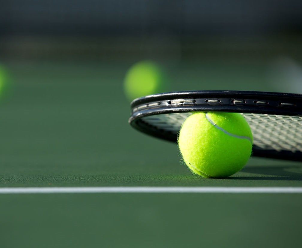 tennis racket and balls on a court