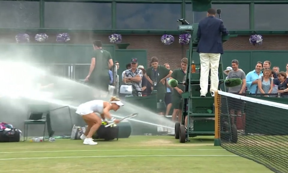 female tennis player being drenched by sprinklers at Wimbledon